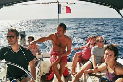 A la barre du voilier loué avec skipper sur la Corse entre amis.