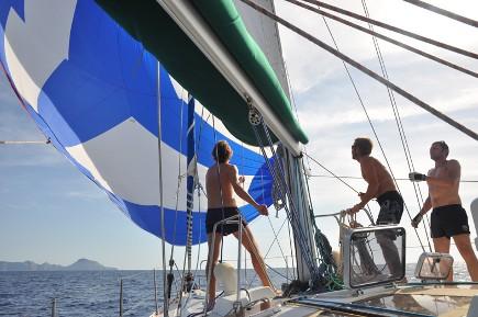 Etablissement du spi sur une croisière entre amis en Corse grâce à la location avec skipper