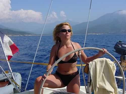 Jeune femme à la barre du voilier de location avec skipper
