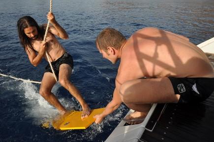 Tentative de surf sur plancher d'un bateau de location avec skipper en Corse