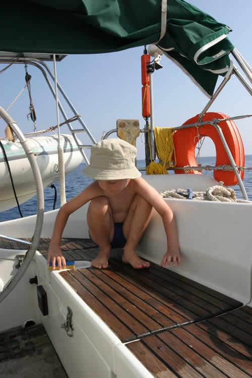 Un enfant à bord du bateau à voile lors d'une location en famille