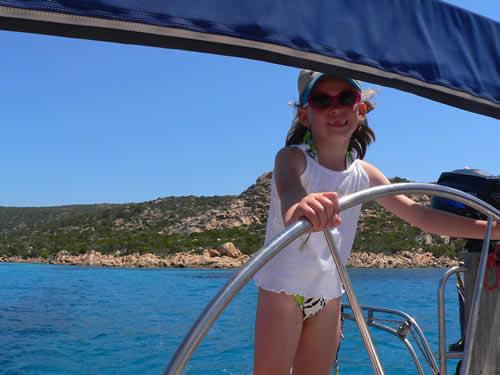 Une gamine à la barre du voilier sur cette location en Corse