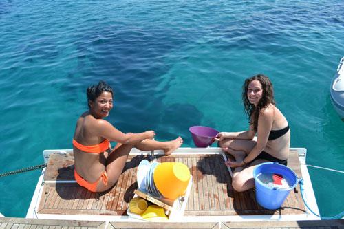 Vaisselle au cul du bateau lors d'une croisière entre amies avec skipper
