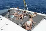 Détente d'une famille sur le trampoline du catamaran loué en Corse avec skipper