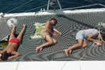 Sieste sur trampoline de catamaran, voilier loué en Corse avec skipper